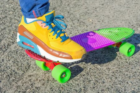 Leg skateboarder on the bright colorful skateboard. Close-up. Shooting on a sunny day Shallow DOF.