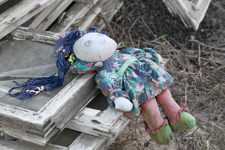 Forgotten children toy. Old rag doll on the ruins.
