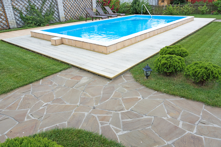 garden furniture: Swimming pool in the yard of a private house with a seating area and garden furniture.