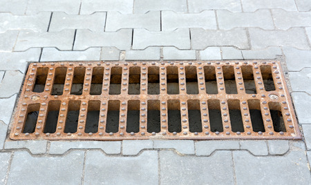 Rusty cast iron storm sewer grating on the sidewalk stacked gray tiles.