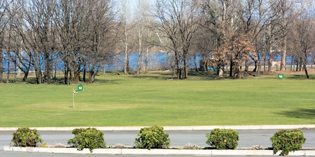 Fragment of golf courses in the city in the early spring. River in the background. Zdjęcie Seryjne