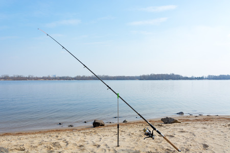 Fishing rod and reel on a river beach spring clear day.