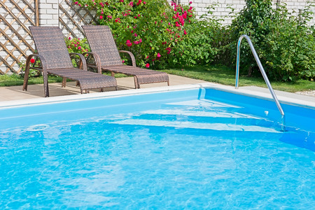 KIEV, UKRAINE - 25 June 2014: Swimming pool with blue water on a sunny day. Recreation area with a fragment of garden and outdoor furniture. Photo Editorial Use Only.