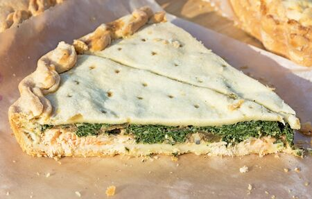 Slice of homemade pie with salmon and spinach. Picture taken at the spring fair under the open sky on a sunny day. Close-up. Zdjęcie Seryjne