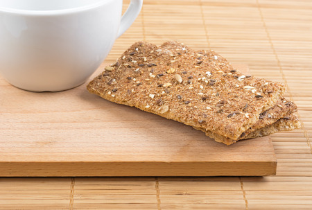 Crispbread with a variety of seeds and white empty cup on the board. Horizontal layout.