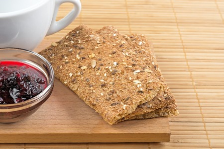 crispbread: Crispbread fragment of white cup and jam in a vase. Stock Photo