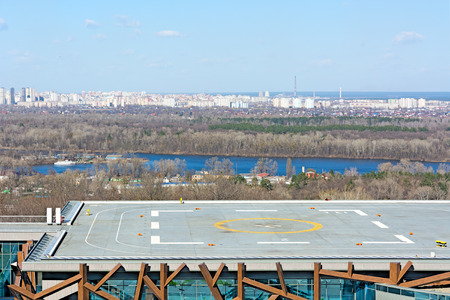 Helipad on the roof of the building on the city background.