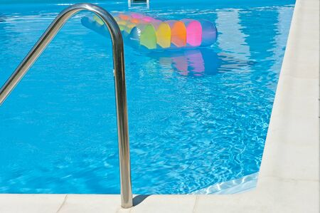 Corner of the swimming pool with blue water and colorful inflatable mattress.
