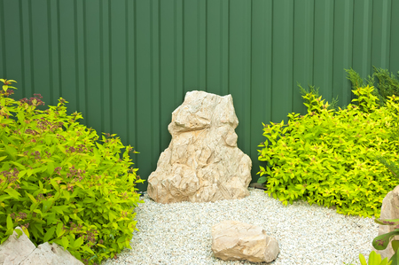 Fragment of the garden with green bushes and bright stones on a background of metal fence.