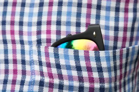 Sunglasses plaid shirt pocket close up. Soft focus. Zdjęcie Seryjne