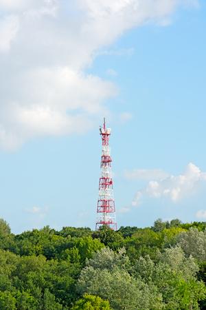 carrera de relevos: La torre de retransmisión en el bosque contra el cielo.