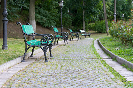 Park walkway of paving stones with benches and street lamps.