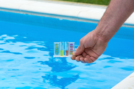 Tester for pool in a hand against the background of the swimming pool.