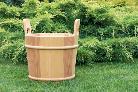 Wooden bucket for sauna in the green grass on a background of juniper. Zdjęcie Seryjne
