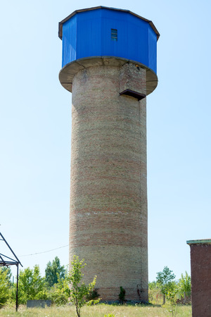 Old brick water tower against the sky. Summer sunny day.