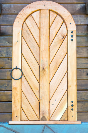 Old wooden door in the wall made of wooden logs. Decoration.