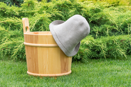 Wooden bucket and felt hat for sauna in the green grass on a background of juniper.