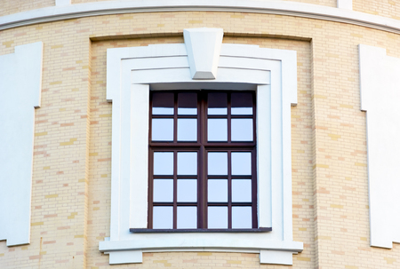Window in the ancient style on a brick wall.