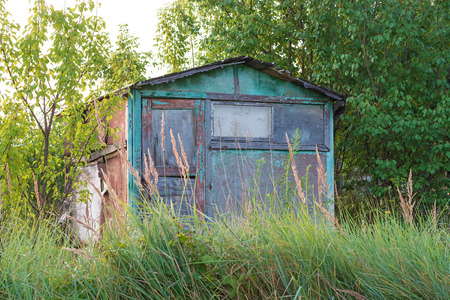 Abandoned garden house surrounded by trees and grass. Shooting at dawn.