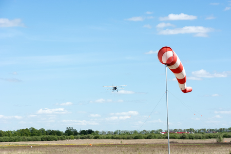 Windsock and going to land the plane on a background of blue sky. Standard-Bild