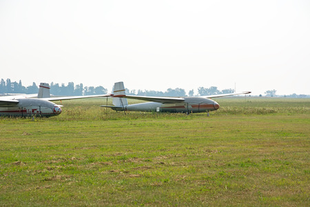 Old gliders parked on the airfield. Picture taken after the rain. Overcast sky covered. Zdjęcie Seryjne - 69127549