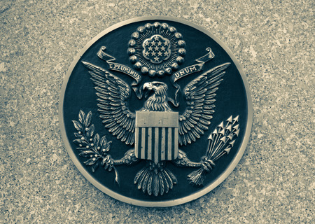 unum: Bronze seal of the United States on marble. toning