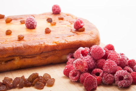 Cottage cheese casserole with raspberries, raisins on a white background photo