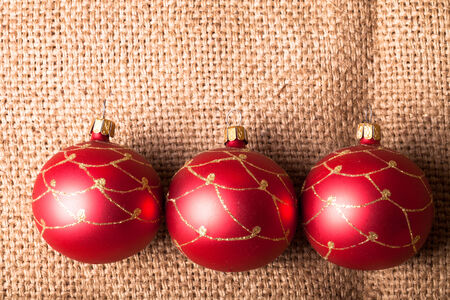 sacking: Three red Christmas tree ball on sacking Stock Photo