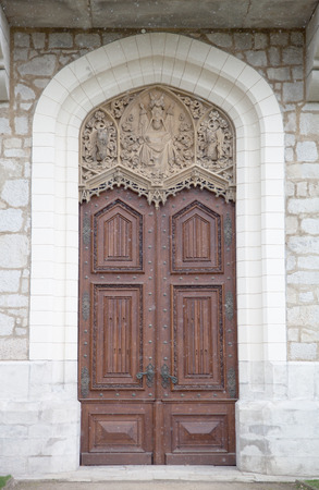 Old wooden door with ornaments in a knights castle. with snowing photo