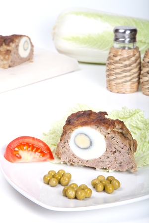 meatloaf with egg tomato and green peas on a white background photo