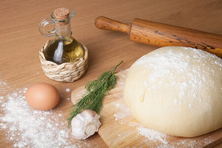 dough on a board with flour. olive oil, eggs, rolling pin, garlic and dill photo