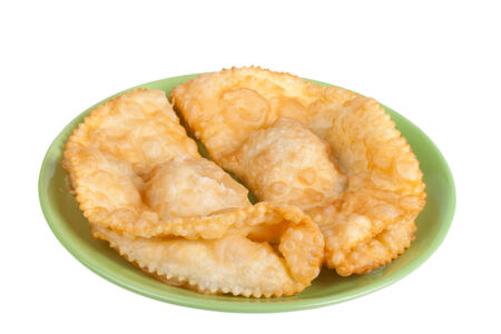cheburek stuffed on a green plate isolated on white background photo