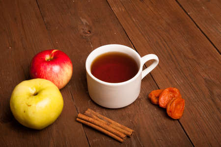 brick earth: Cup of tea on old wooden table with two apples, dried apricots and cinnamon Stock Photo