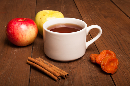 fireclay: Cup of tea on old wooden table with two apples, dried apricots and cinnamon Stock Photo