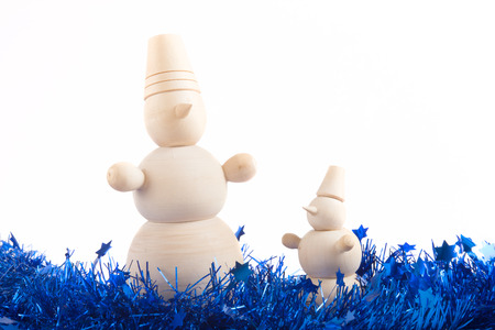 two wooden snowman standing in tinsel for holiday decorations photo