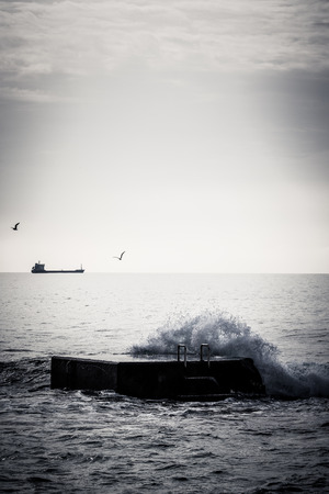 Breaking Waves on Pier in black and white colors photo