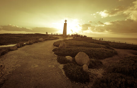 tourists watching the sunset near the cross monument at Cabo da Roca, the western point of Europe - Portugal photo