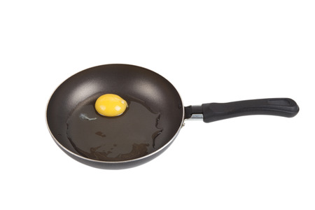 raw egg in a frying pan isolated on white background photo