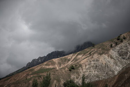 wheather: Clouds at the mountains. Stormy wheather. Toned. Dramatic