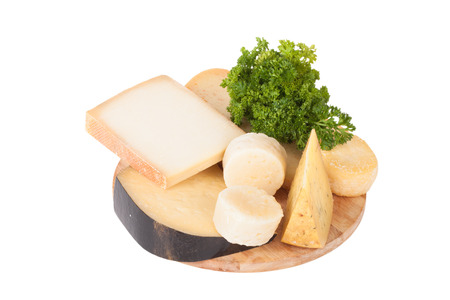 cheese platter: Different cheeses and a bunch of parsley lying on a board isolated on white background