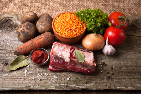 Ingredients for Turkey vegetable soup with red lentils, lying on an old wooden board and sacking photo