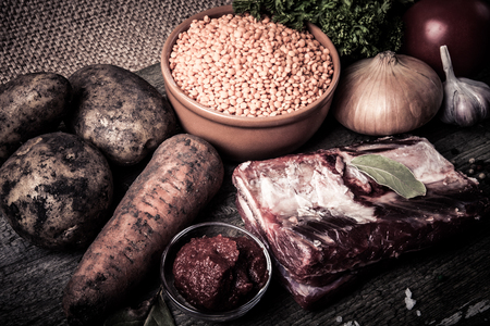 Ingredients for Turkey vegetable soup with red lentils, lying on an old wooden board and sacking. Tinted photo