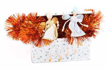 two angels sitting on a box with tinsel. On a light background