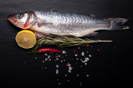 Fresh sea fish lying on dark background with spices. Space for text