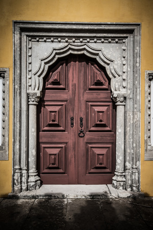 old wooden door framed by a carved stone. tinted photo