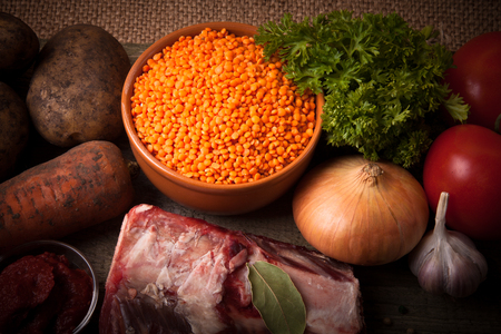 Ingredients for Turkey vegetable soup with red lentils, lying on an old wooden board and sacking. photo