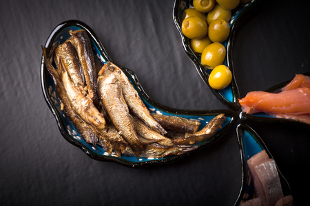 assortment: Fish assortment and olives on magic plates on a dark background