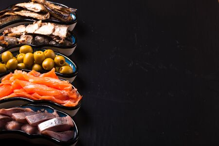 mollusk: Fish assortment and olives on a plate on a dark background. With space for text Stock Photo