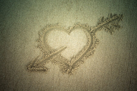 Heart drawn in the sand. Beach background. Top view. Tinted photo