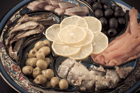 mollusk: Assorted fish on a plate on a dark background.
